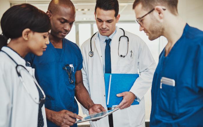 Multiracial-Doctors-Review-Patient-Records-Tablet-1200